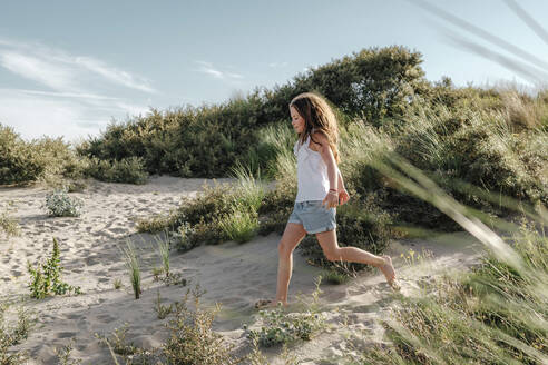 Girl running on sand at beach during sunny day - OGF00613