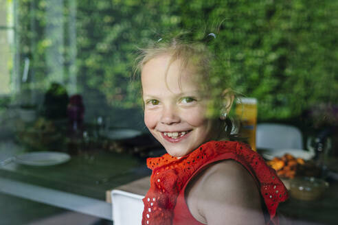 Smiling girl looking through window on sunny day - OGF00619