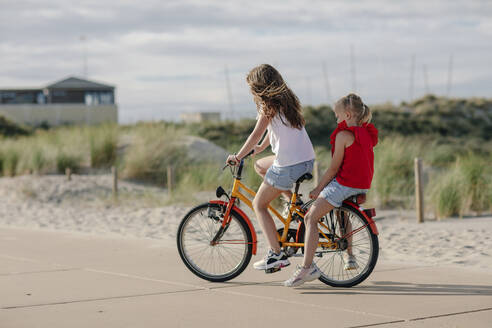Sisters riding on bicycle during sunny day - OGF00625