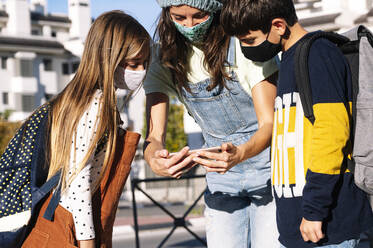 Mother and kids wearing protective face mask using smart phone standing in public park on sunny day - JCMF01549
