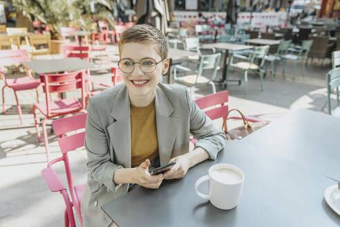 Woman looking away while using smart phone sitting in outdoor cafe - MFF06706
