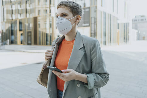 Woman looking away wearing protective face mask using smart phone standing on street in city - MFF06739