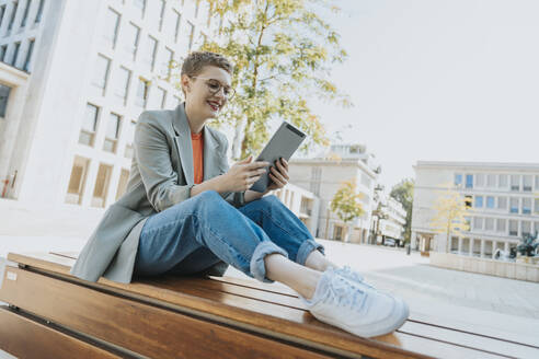 Woman using digital tablet while sitting on bench during sunny day - MFF06751