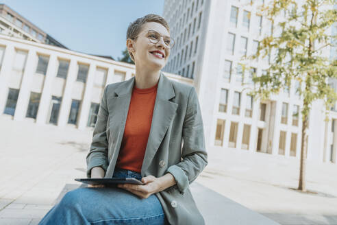 Woman smiling while holding digital tablet sitting on street during sunny day - MFF06757
