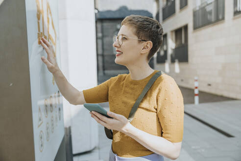 Mid adult woman reading map while holding smart phone standing in city on sunny day - MFF06760