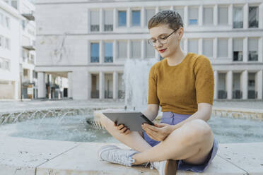 Woman with cross legged using digital tablet sitting by fountain on sunny day - MFF06769