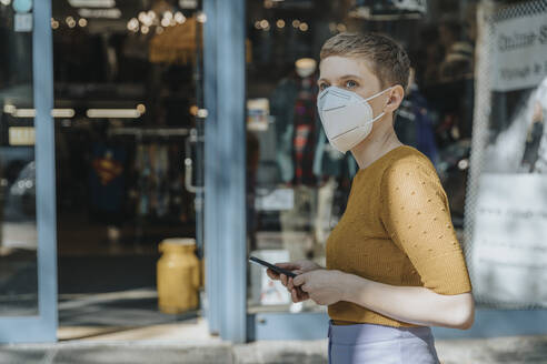 Woman wearing protective face mask holding smart phone looking away while standing in city - MFF06775