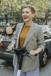 Cheerful woman riding electric push scooter on street in city - MFF06778