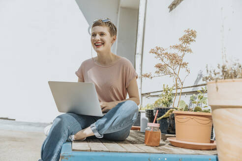 Woman laughing while using laptop sitting on terrace during sunny day - MFF06781