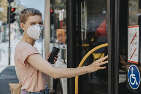 Woman wearing protective face mask catching bus on street in city - MFF06784
