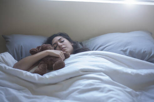 Young woman holding toy while sleeping on bed at home - AJOF00434