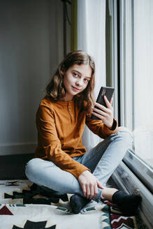 Girl with mobile phone sitting cross legged by window at home - EBBF01108
