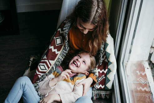 Playful girl laughing while lying on sister lap at home - EBBF01114