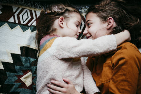 Sisters with arm around lying on blanket at home - EBBF01120