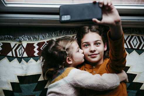 Girl kissing sister while taking selfie through mobile phone at home - EBBF01123