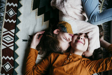 Girl embracing sister face while lying on blanket at home - EBBF01126