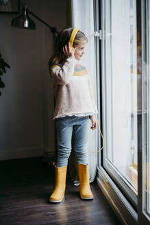 Girl wearing headphones looking through window while standing at home - EBBF01129