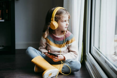 Girl wearing headphones using mobile phone while sitting by window at home - EBBF01132