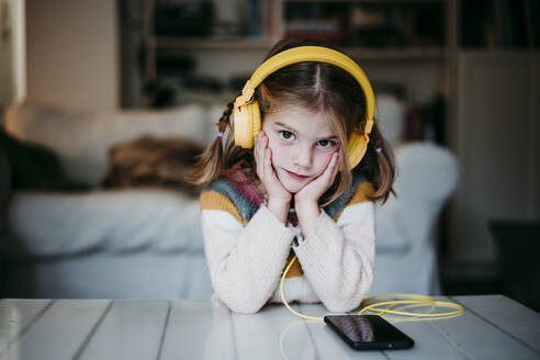 Girl wearing headphones leaning on table with head in hands at home - EBBF01135