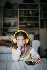 Girl wearing headphones looking away while leaning on table at home - EBBF01138
