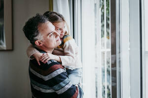Father carrying daughter while standing by window at home - EBBF01141