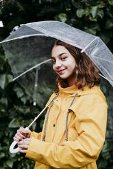 Smiling girl in raincoat holding camera while standing against leaf wall - EBBF01165