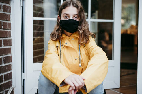 Girl wearing protective face mask sitting on floor against door - EBBF01177