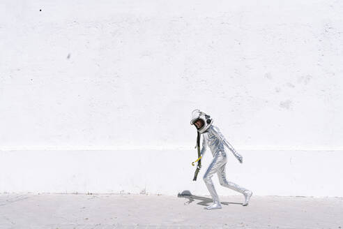 Boy wearing astronaut costume running against wall in city - JCMF01587