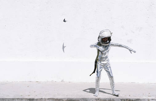 Boy in astronaut costume playing while standing against wall in city - JCMF01590