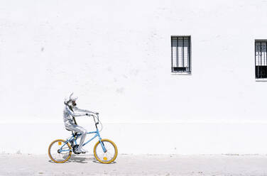 Playful boy in astronaut cycling bicycle against wall - JCMF01593