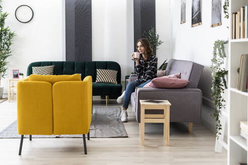 Woman drinking coffee while sitting in living room on sofa at home - GIOF09331
