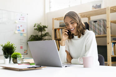 Smiling businesswoman talking on mobile phone while working on laptop at office - GIOF09382