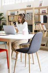 Businesswoman using mobile phone while sitting at office - GIOF09388