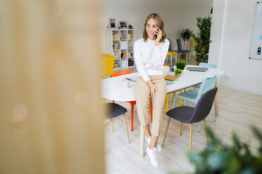 Businesswoman talking on mobile phone while sitting on table at office - GIOF09394