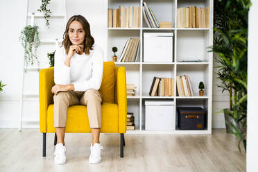 Young businesswoman sitting with head in hands on sofa at office - GIOF09397