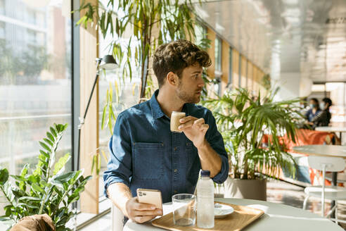 Businessman looking away while drinking coffee at table in cafe - VABF03737