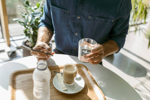Businessman using smart phone while drinking water in glass at table in restaurant - VABF03743