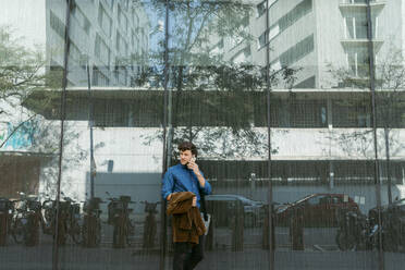 Young businessman leaning on wall of modern glass building while talking on smart phone - VABF03770