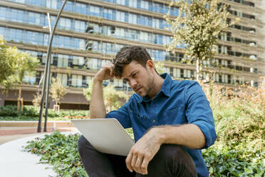 Confused young businessman using laptop while sitting against office buildings - VABF03782