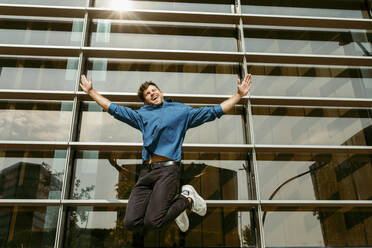 Carefree young businessman jumping against modern office building - VABF03794