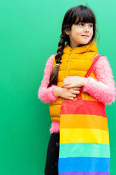 Girl carrying colorful bag looking away while standing against green wall - ERRF04654