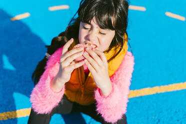 Cute girl eating donut while sitting on basketball court - ERRF04657