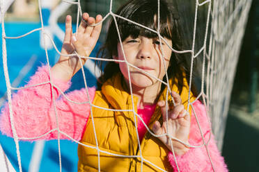 Cute girl seen through net of goal post during sunny day - ERRF04660
