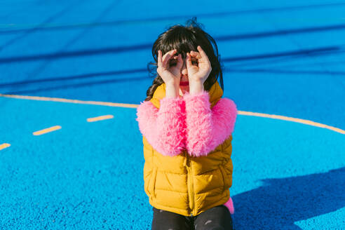 Girl forming binoculars with fingers while sitting at sports court - ERRF04663