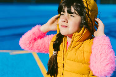 Cute girl in warm clothing looking away while sitting on sports court - ERRF04666