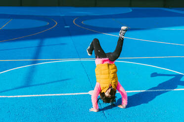 Playful girl practicing handstand on soccer court - ERRF04669