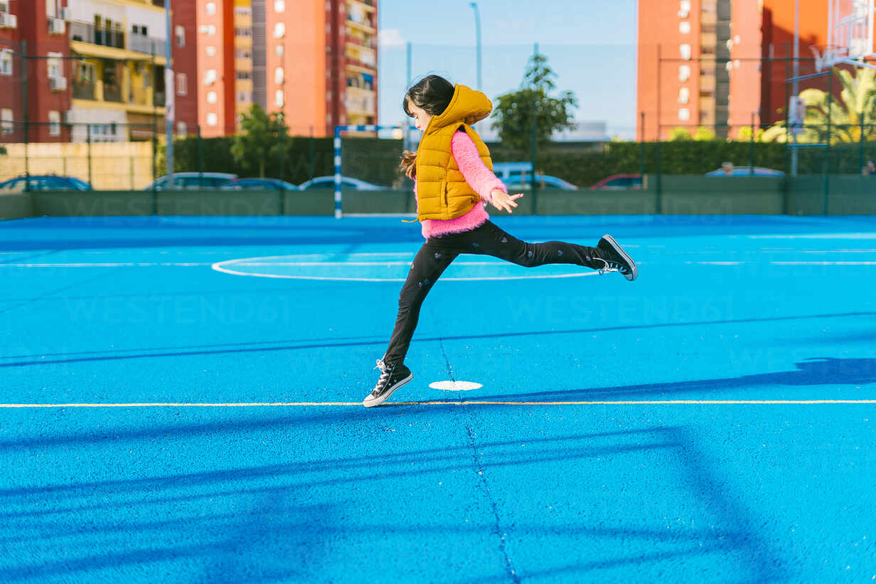 Girl jumping on blue sports court during sunny day - ERRF04672 - Eloisa Ramos/Westend61