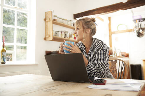 Senior woman looking away while drinking coffee sitting with laptop in kitchen at home - PMF01492