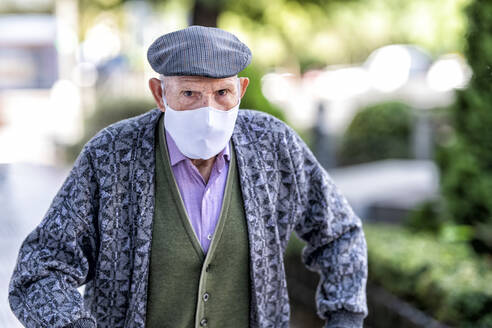 Senior man wearing protective face mask standing outdoors during COVID-19 - GGGF00024