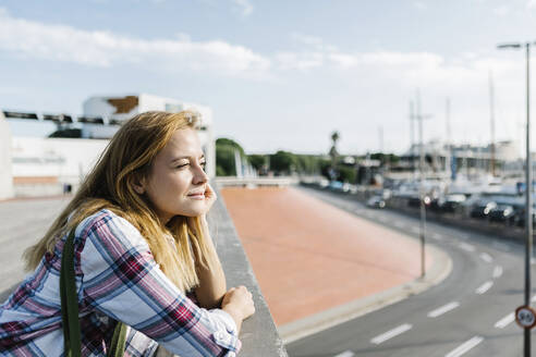 Thoughtful woman with hand on chin standing in city during sunny day - XLGF00687